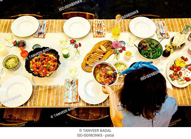 Woman placing dish on dining table