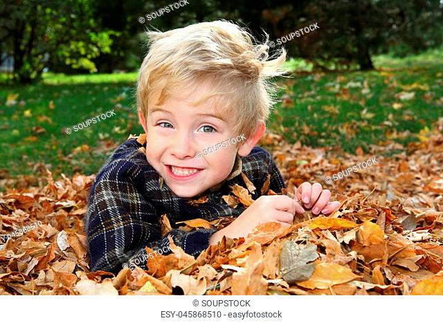 Smiling boy playing in a leaf pile