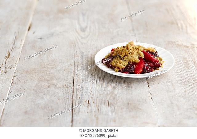 Apple and blackberry crumble on a plate