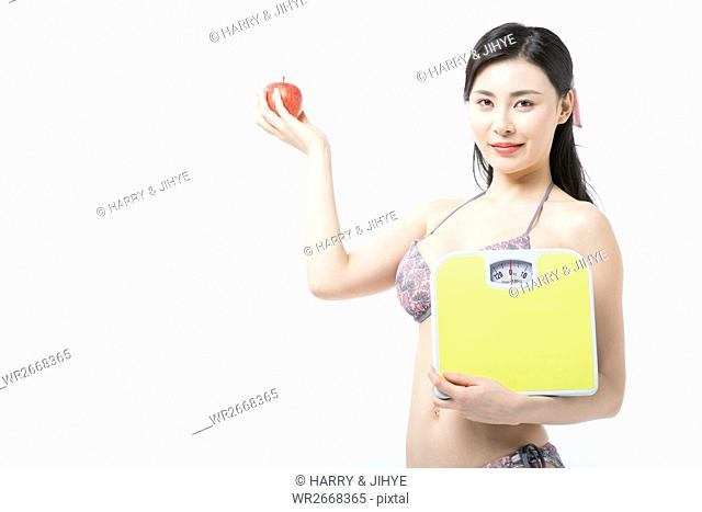 Young smiling woman in bikini posing with an apple and a scale