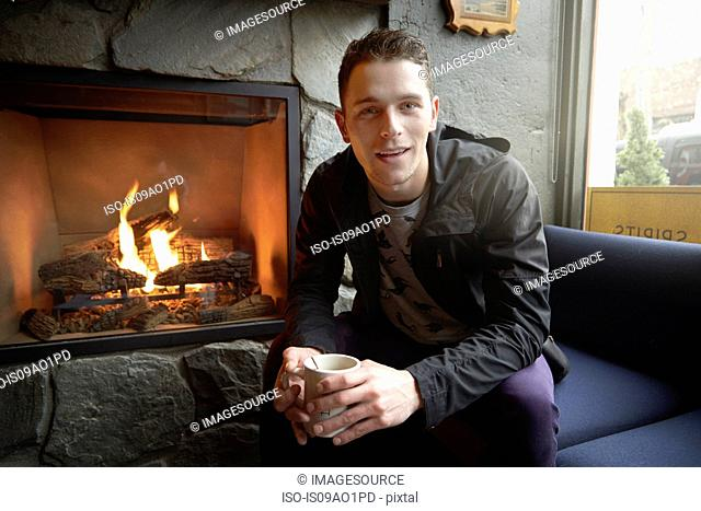 Portrait of young man sitting by open fire in cafe