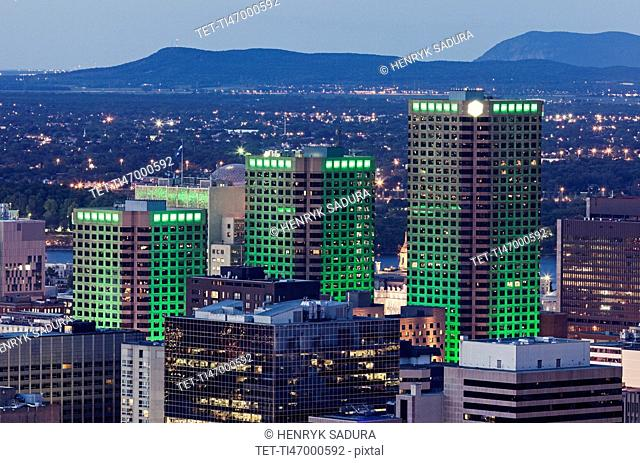 Three skyscrapers illuminated with green light towering over cityscape