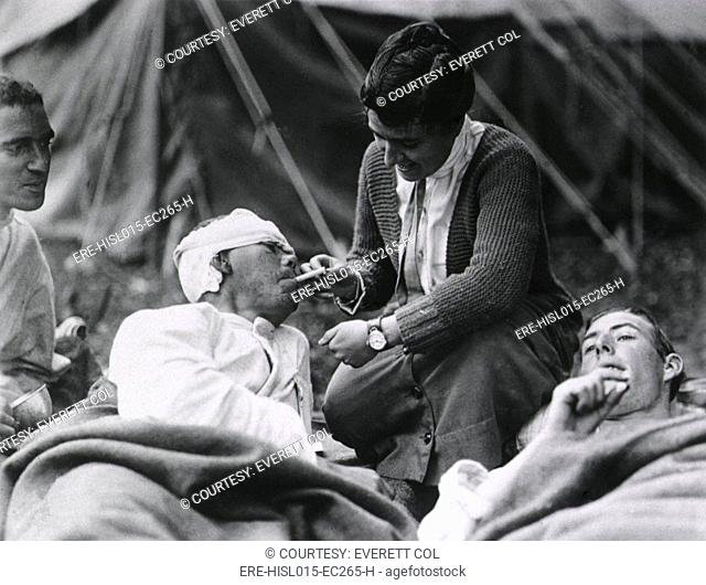 Red Cross Worker Miss Anna Rochester, of the Smith College Unit, helping a wounded soldier with his cigarette at the U.S