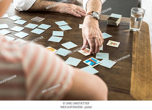 Senior man playing memory with his grandson