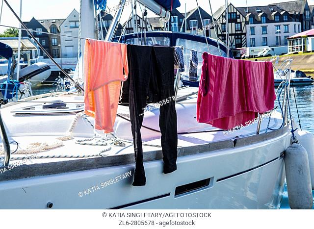 Laundry hanged on the sail of the sailboat to dry as there are no washer and dryer on a boat