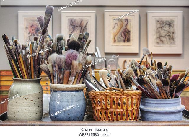 Jars of paintbrushes on desk
