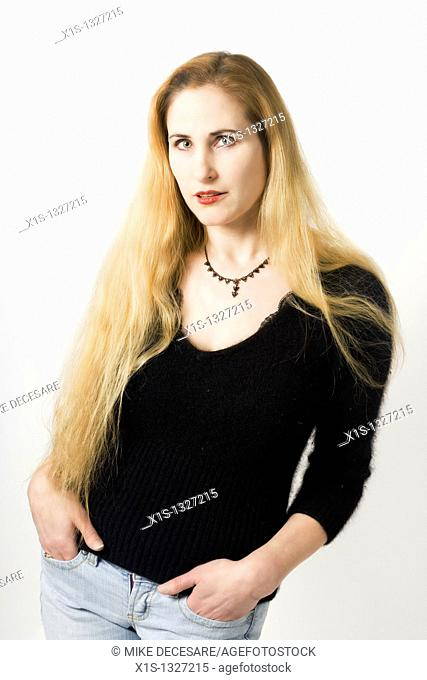 Woman with very long blond hair, wearing blue jeans and a black top, has her hands in her pockets and leans back as she looks at the camera