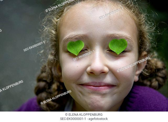 Austria, Girl (10-12) with heart shaped clover leaves on her eyes