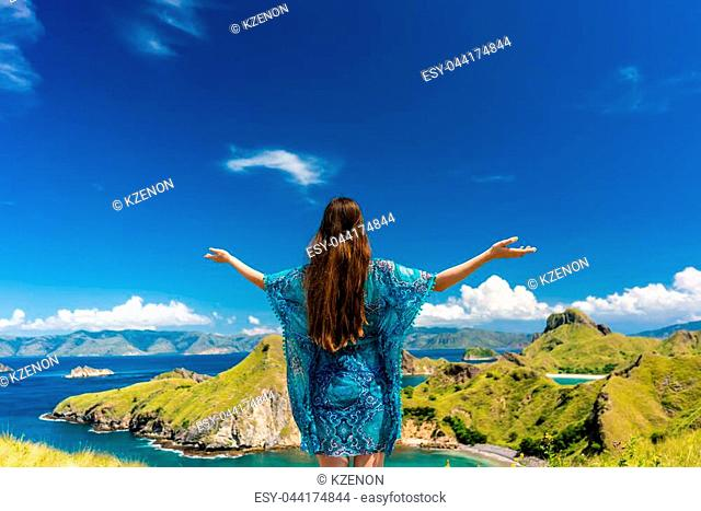 Rear view of a happy tourist enjoying the breeze while standing with outstretched arms outdoors during summer vacation in Padar Island, Indonesia