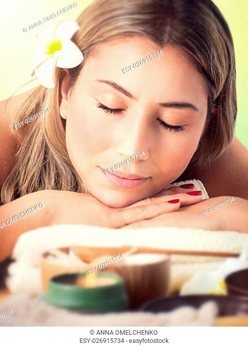 Closeup portrait of a peaceful woman with closed eyes lying down on a massage table in the spa salon, healthy lifestyle