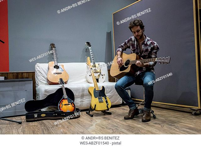 Man playing guitar in a recording studio