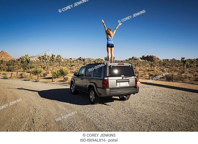 Runner jubilant standing on car, Joshua Tree National Park, California, US