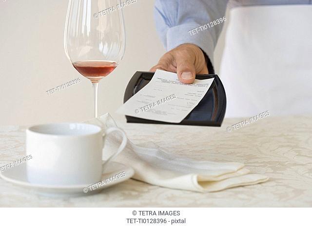 Waiter leaving check on table