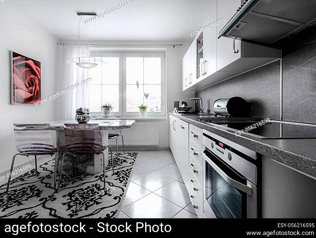 Kitchen currently at home with classical style, decorated in white with marble fittings and big bright window