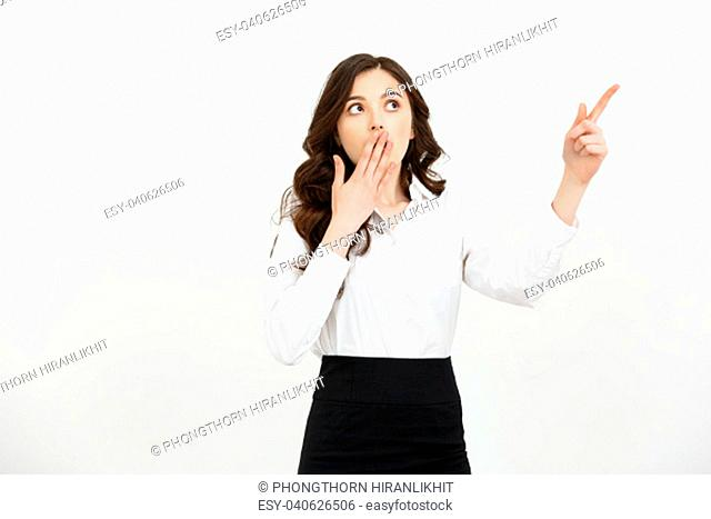 Business Concept: Portrait of surprised young businesswoman pointing finger away to copy space. Isolated on a white background