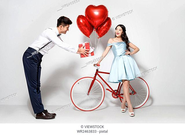 Young couple with heart-shaped balloons and gift
