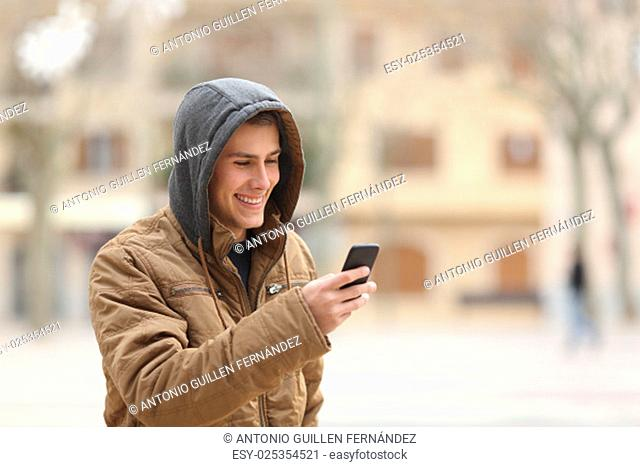 Happy teen boy walking on the street and using a smart phone