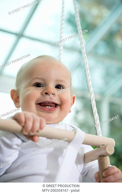Portrait of laughing toddler sitting in a swing
