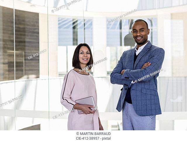 Portrait smiling, confident business people at office window