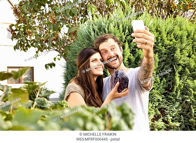 Couple taking a selfie in the garden with red cabbage