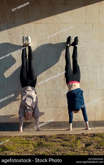 Two young women acrobat doing handstand on the wall with cityscape on background, close up