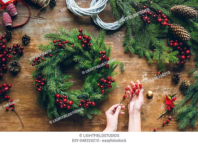 top view of florist hands making Christmas wreath with fir branches and decorative berries on wooden tabletop