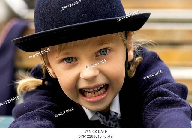 Portrait of a young girl wearing blue sweater and felt hat looking into the camera; London, England