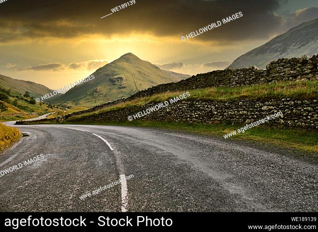 Kirkstone Pass A592 road winding through the breathtaking scenery of the Lake District National Park at dusk, Cumbria, England