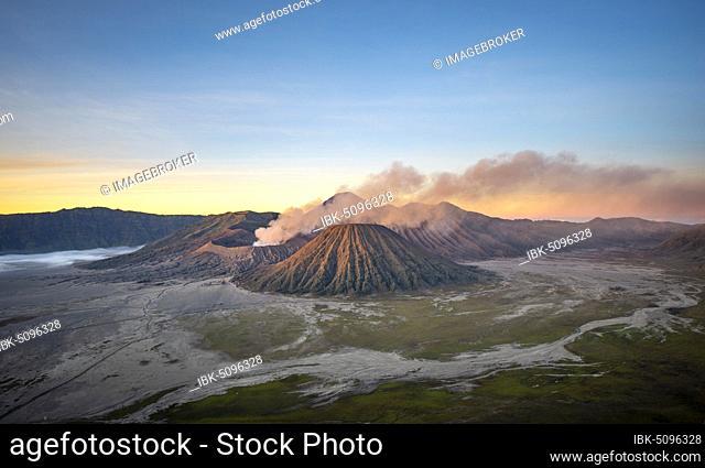 Volcanic landscape at sunrise, smoking volcano Gunung Bromo, with Mt. Batok, Mt. Kursi, Mt. Gunung Semeru, Bromo-Tengger-Semeru National Park, Java, Indonesia