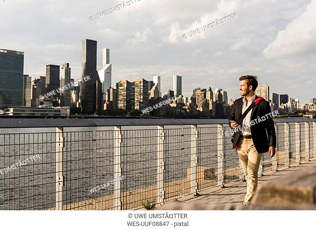 USA, New York City, businessman walking along East River