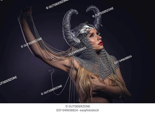 Steel, Viking goddess, beautiful young blond woman with horned helmet made of iron. Fantasy image and stories