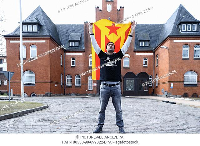 30 March 2018, Germany, Neumuenster: Catalan protestor Jimmy Jump (real name: Jaume Marquet i Cot) waves the leftist Catalan flag, the estelada groga