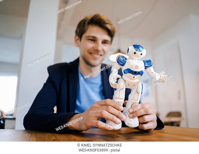 Smiling man holding robot