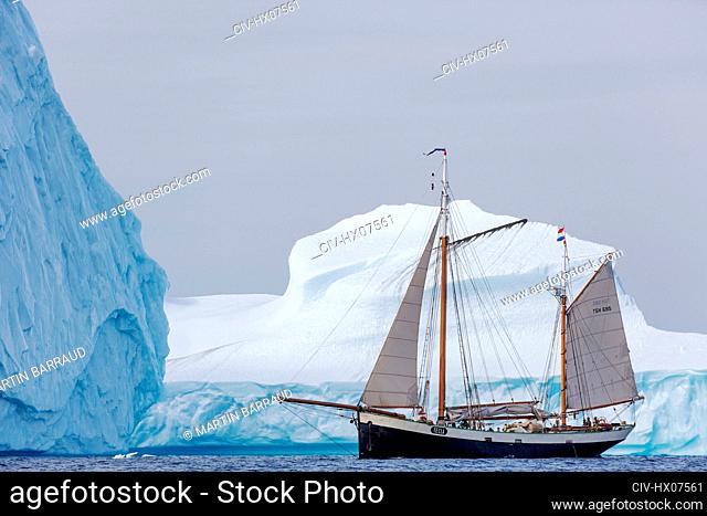Ship sailing past large icebergs Greenland