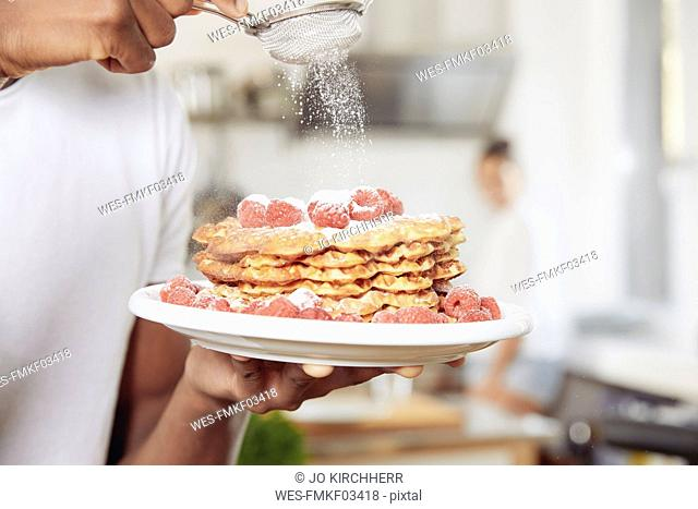 Young man sprinkling icing sugar on stack of waffles, close-up