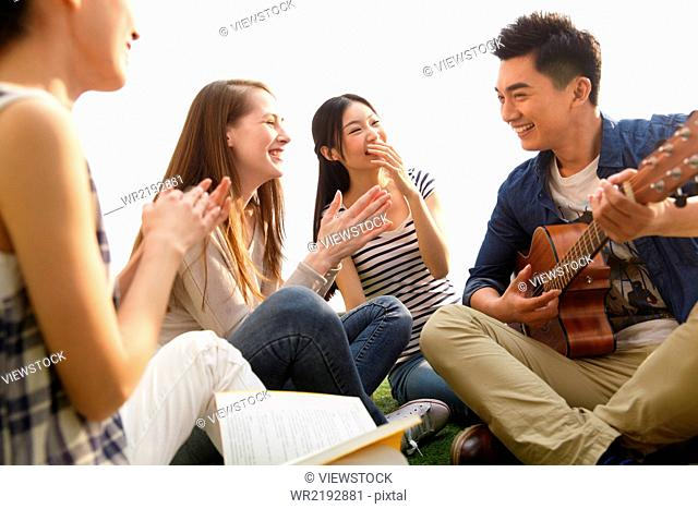 Young people sitting on lawn singing