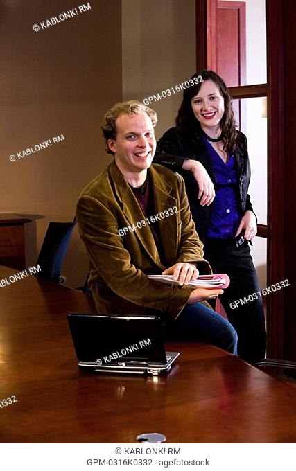 Portrait of businessman and businesswoman in boardroom