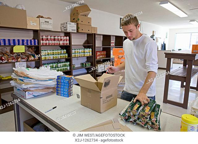 Alamosa, Colorado - A high school student from First United Methodist Church in Chula Vista, California stocks the shelves of a food bank operated by La Puente...