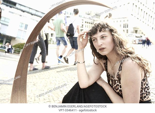 young thoughtful woman observing passersby in city Berlin, Germany