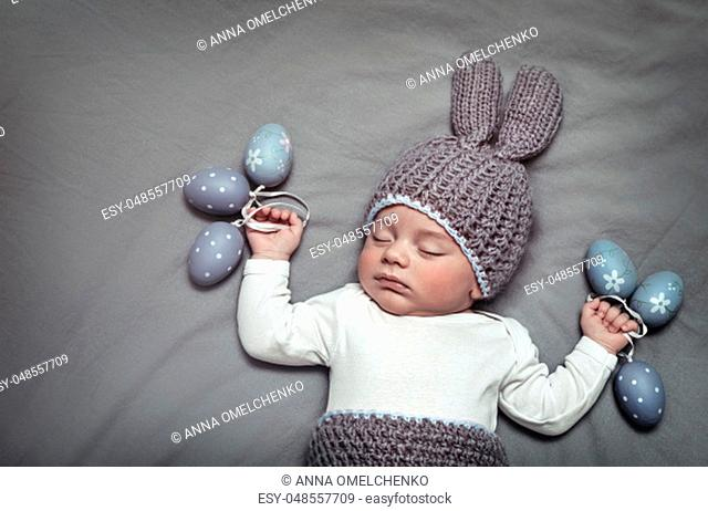 Cute little baby wearing festive Easter costume, sleeping on the gray blanket with decorated eggs, christians holiday, photo with a copy space