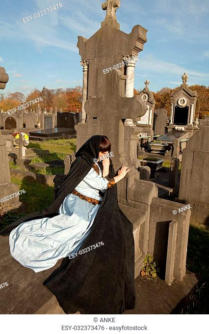 Young woman lying on a tombstone in a victorian dress