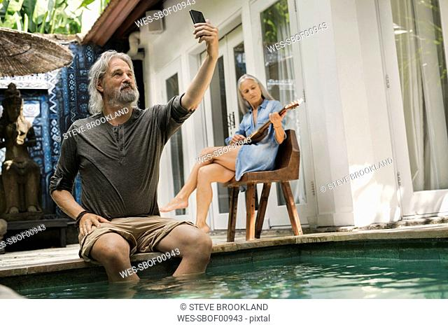 Senior man taking selfie at poolside while his wife is playing the guitar