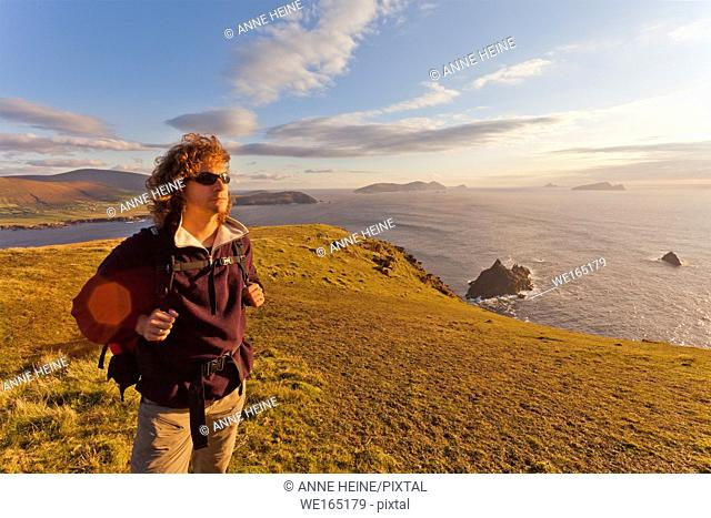 man standing on cliffs with islands in background lit from behind, dingle peninsula, ireland
