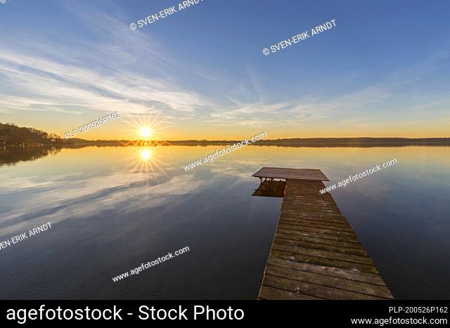 Wooden jetty at Großer Plöner See / Great Plön Lake / Lake Plön / Grosser Ploener See at sunset in winter, Schleswig-Holstein, Germany