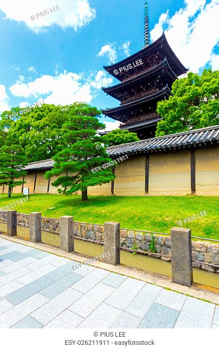 Toji five story pagoda seen from outside its wall on a clear, sunny, blue sky day in Kyoto, Japan. Vertical