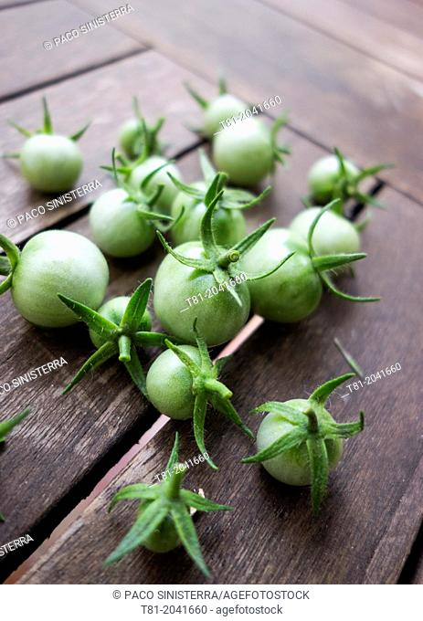 Green cherry tomatoes on wooden table