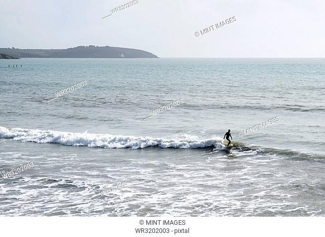 Surfer wearing wet suit riding ocean wave close to shore