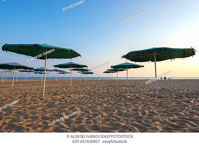 Opened sandy beach umbrellas at sunset