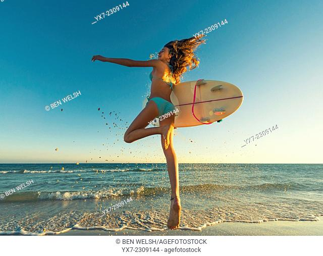 Young teenager with her surf board at the beach. Tarifa, Cadiz, Costa de la Luz, Andalusia, Spain