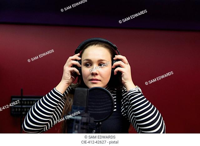 Teenage girl musician recording music, singing in sound booth